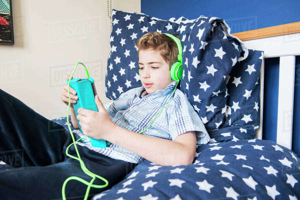 A ten year old boy laying on a bed listening to music on earphones Royalty-free stock photo