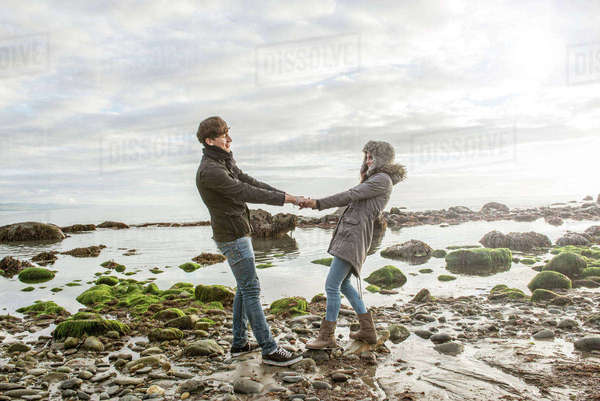 A young couple holding hands on the beach at Porthmadog Royalty-free stock photo