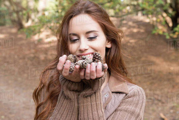 A young woman standing with a handful of pine cones in a forest in Autumn Royalty-free stock photo