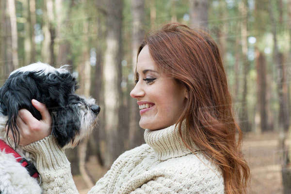 A young woman stroking a dog on a forest walk in Autumn Royalty-free stock photo