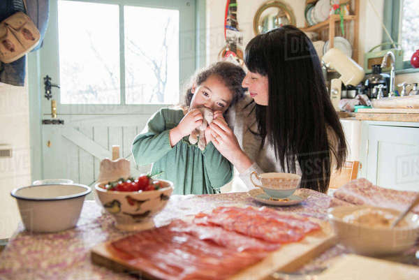 A six year old girl being comforted by her mother at the dinner table Royalty-free stock photo