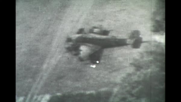 Machine gun firing from plane, several POV clips from plane firing machine gun on ground targets and hitting a German plane from the air.  Pilot ejected with parachute.  Tracer bullets can be seen hitting targets. Rights-managed stock video