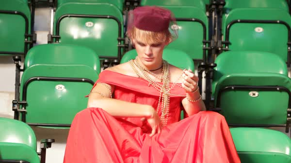 Man in a red dress sitting on green bleachers playing with beads Royalty-free stock video
