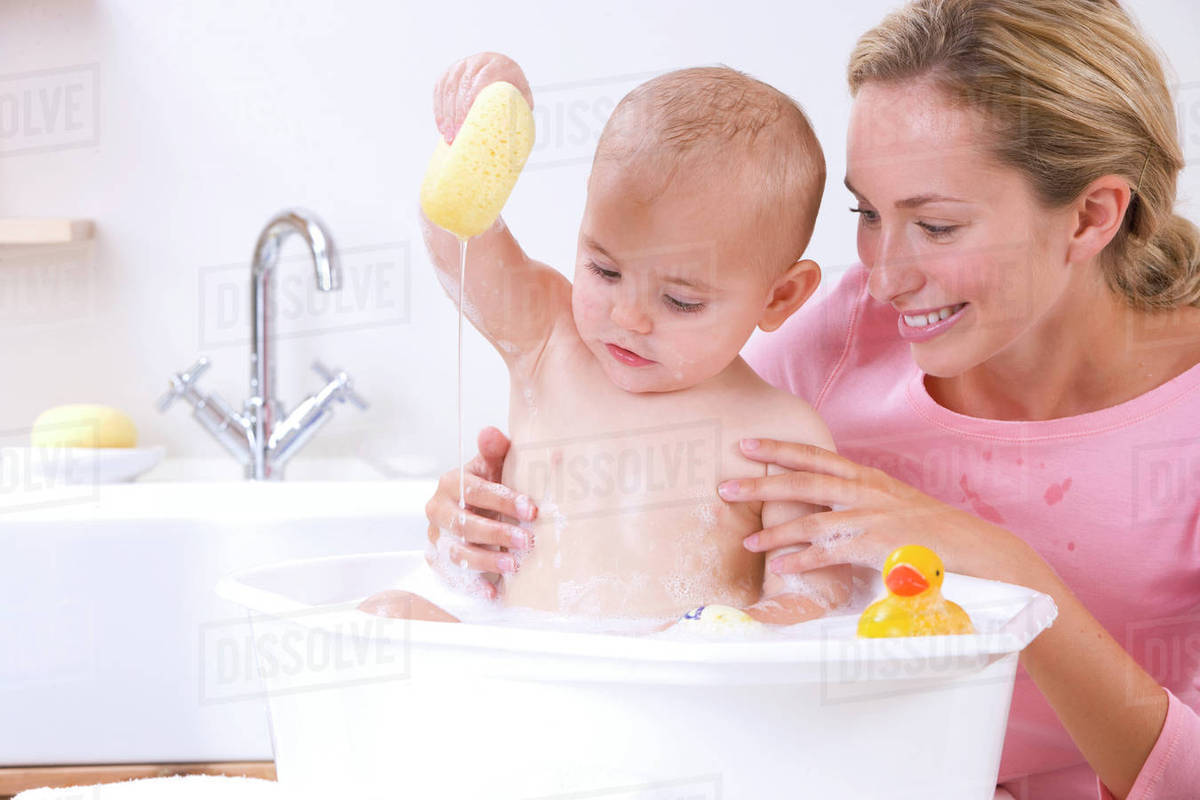 Mother giving baby boy a bath in basin - Stock Photo - Dissolve