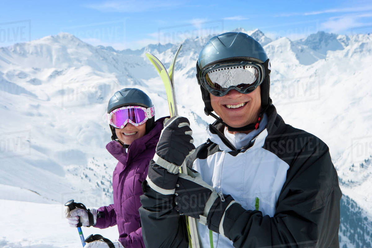6c81fa39546 Portrait of smiling senior couple wearing ski goggles and holding skis on  snowy mountain