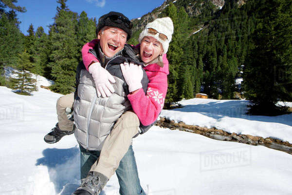 Playful couple piggybacking in snowy woods Royalty-free stock photo