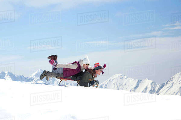 Senior couple sledding on snowy mountain Royalty-free stock photo