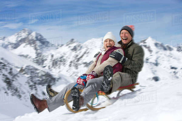 Enthusiastic senior couple sledding down slope on snowy mountain Royalty-free stock photo