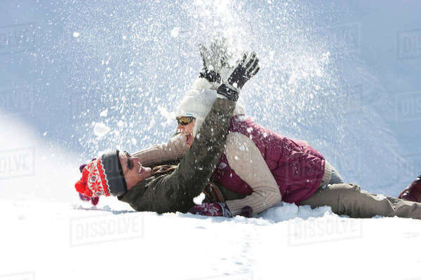 Playful senior couple laying and throwing snow Royalty-free stock photo