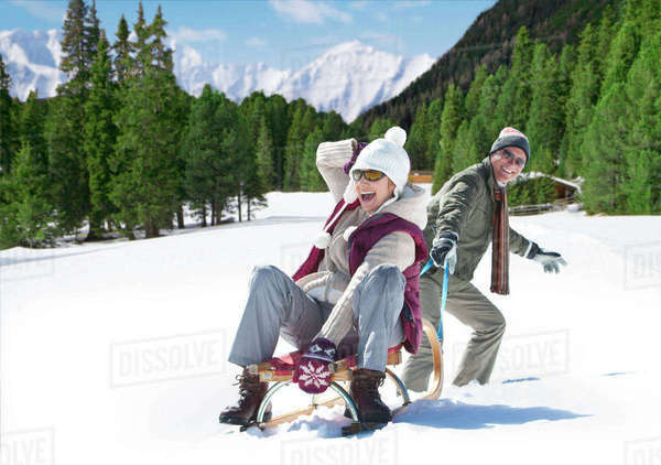 Smiling senior couple sledding in snowy woods Royalty-free stock photo