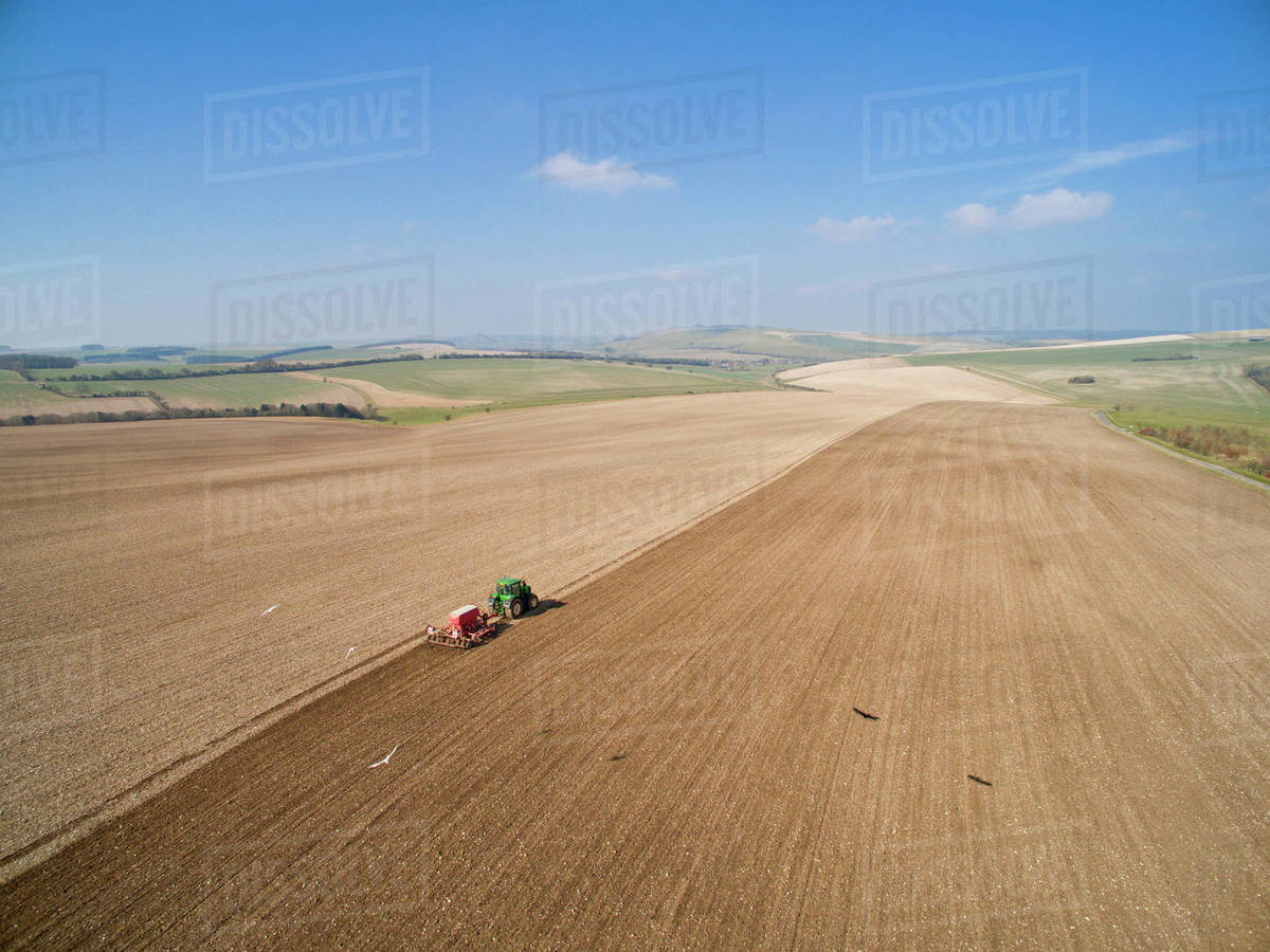 Aerial View Of Tractor Pulling Drill Sowing Seed In Field stock photo