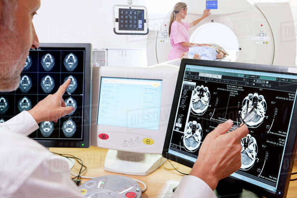 Doctor comparing CT scan digital brain scan in hospital Royalty-free stock photo