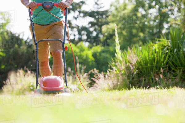 Man pushing lawn mower, mowing grass in sunny summer yard Royalty-free stock photo