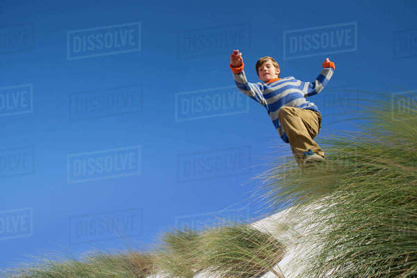 Exuberant boy jumping over sand dune beach grass Royalty-free stock photo