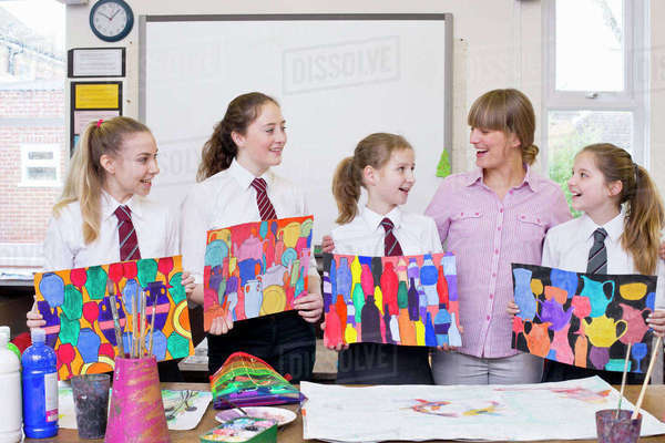 Smiling art teacher and middle school students showing paintings in art class Royalty-free stock photo