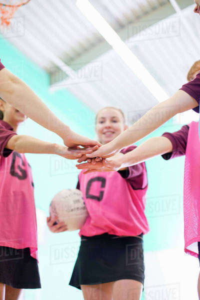 High school students touching hands in huddle before volleyball game Royalty-free stock photo
