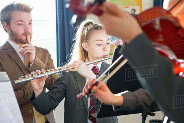 Teacher teaching high school students playing flute and violin in music class Royalty-free stock photo