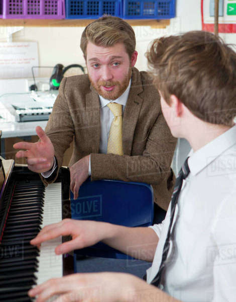 Music teacher guiding high school student playing piano Royalty-free stock photo