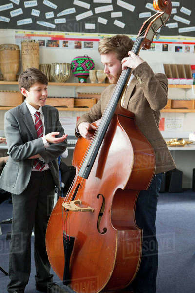 Music teacher guiding middle school student playing double bass in music class Royalty-free stock photo