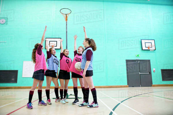 Enthusiastic high school students cheering before netball game in gym Royalty-free stock photo