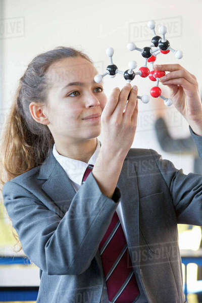 Smiling high school student examining molecule model in science class Royalty-free stock photo