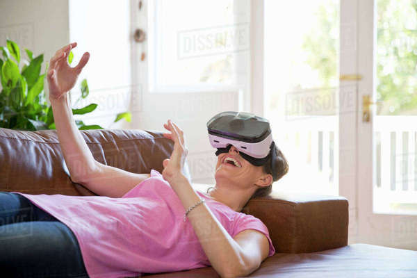 Woman Lying On Sofa Interacting With Virtual Reality Headset Royalty-free stock photo