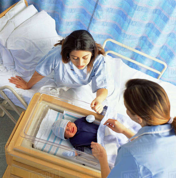 Nurse and mother checking on crying baby in hospital Royalty-free stock photo