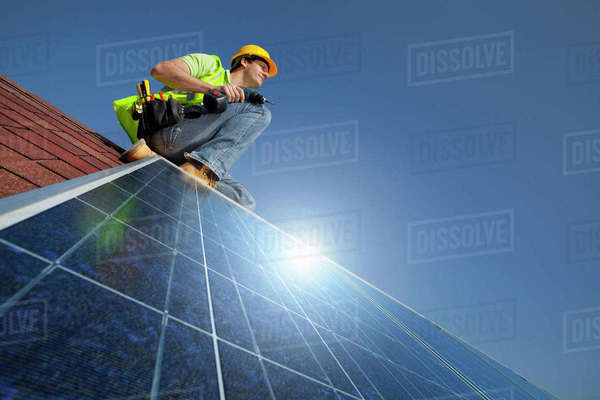Engineer installing solar panel on rooftop Royalty-free stock photo