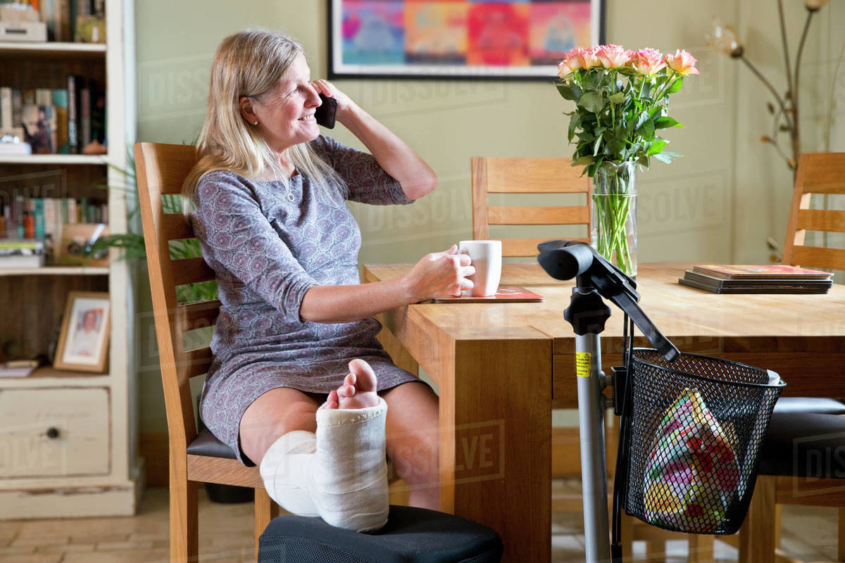 Mature Woman With Leg In Plaster Cast Sitting By Table At Home
