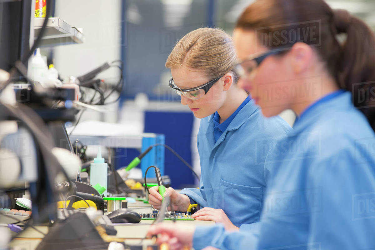 technicians soldering circuit boards on production line intechnicians soldering circuit boards on production line in manufacturing plant