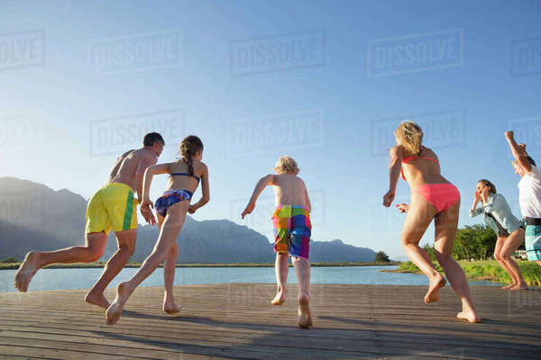 Multi generation family running to jump into lake from a jetty Royalty-free stock photo