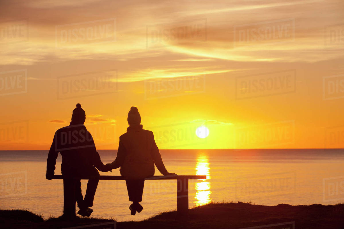 Silhouette Of Couple Sitting On Bench Holding Hands