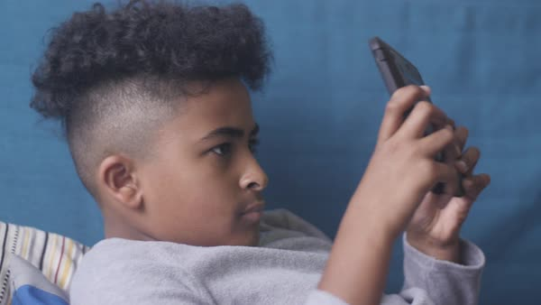 Hand-held shot of a boy looking at a tablet Royalty-free stock video