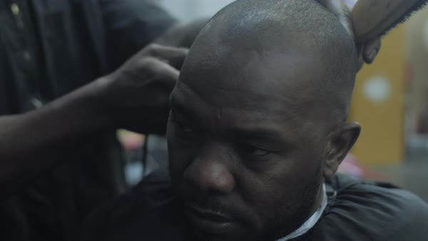 Close-up of a barber using an electric hair trimmer to shave a man's head Royalty-free stock video
