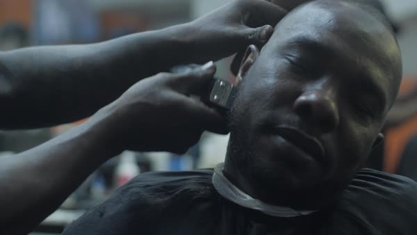 Close-up of a barber trimming a man's beard with an electric razor  Royalty-free stock video