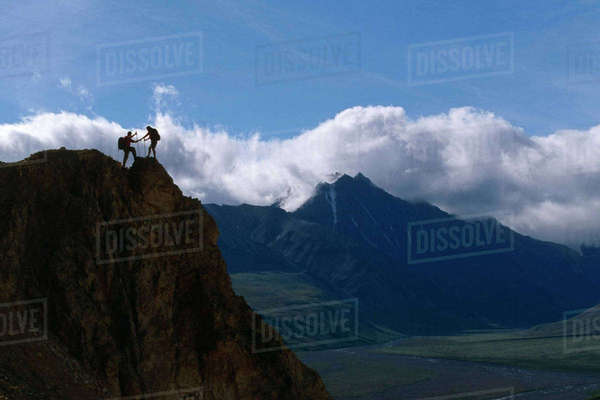 Couple Hiking Along Rock Outcrop at Denali National Park Interior Alaska Summer Scenic Rights-managed stock photo