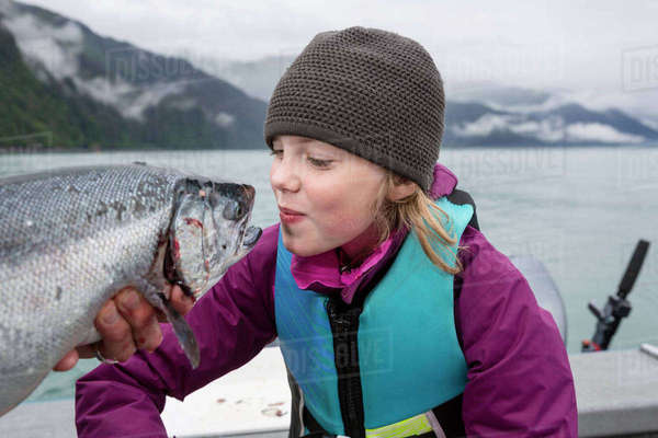 Young Girl Pretends To Kiss A Fish On The Lips, Seward, Southcentral Alaska, USA Rights-managed stock photo
