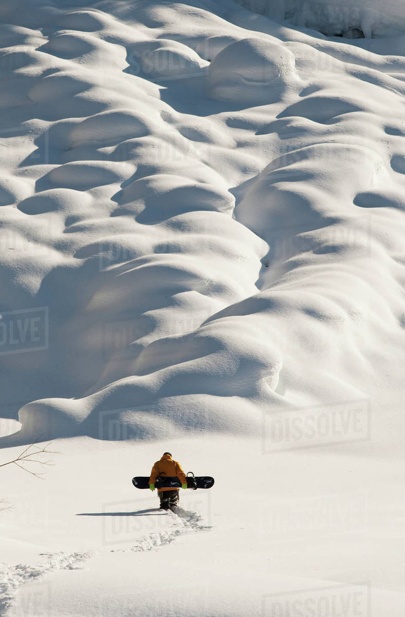 Person walking with a snowboard in mountains above Haines, Southeast Alaska, USA Rights-managed stock photo