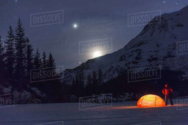Nighttime view of a man standing next to a lit tent on a snow covered Trail Lake with the moon, stars, and planets overhead, Moose Pass, Kenai Peninsula, Southcentral Alaska Rights-managed stock photo