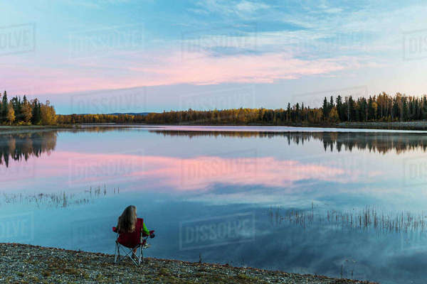Woman relaxes at sunset at the edge Chena River Lakes near Fox, Interior Alaska Rights-managed stock photo
