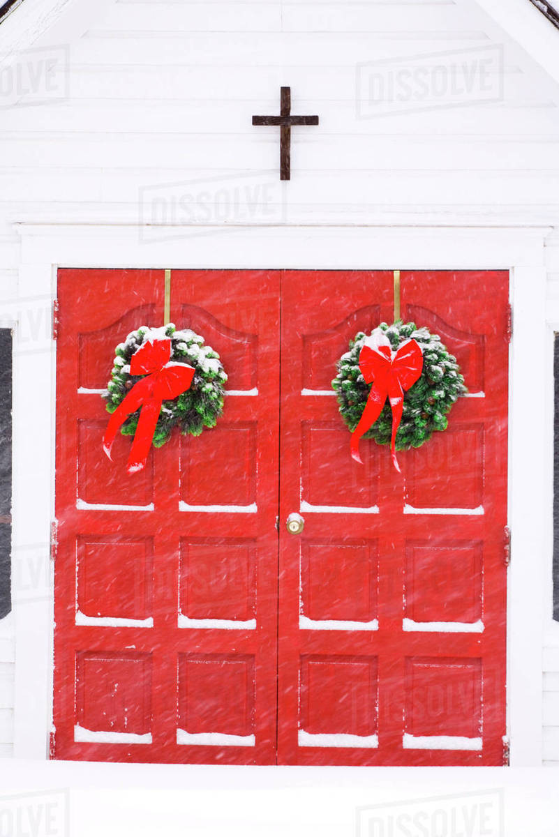 Christmas Wreaths Hang On Bright Red Double Doors At An Episcopal