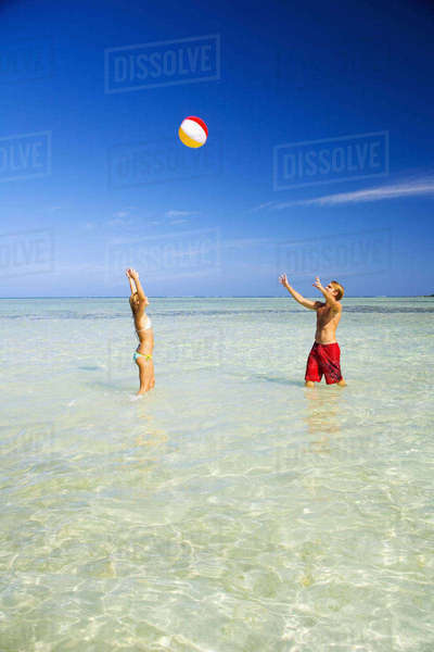 Hawaii, Oahu, Kaneohe, Couple Playing With Beach Ball In Crystal Clear Water At The Sandbar Or Dissapearing Island Rights-managed stock photo