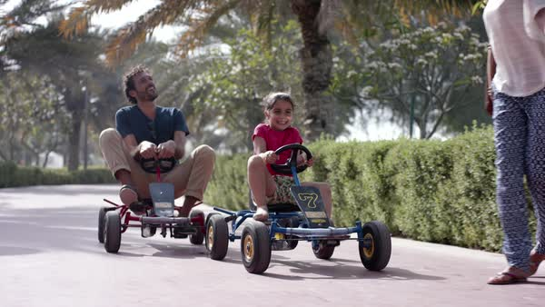 Parents with daughter driving pedal go kart at park. Royalty-free stock video