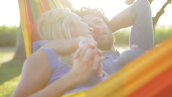 Couple lying together in hammock, holding hands and talking Royalty-free stock video