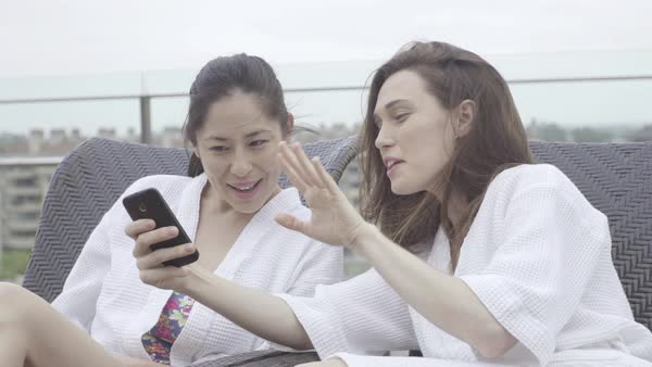 Women looking at smartphone while relaxing at spa Royalty-free stock video