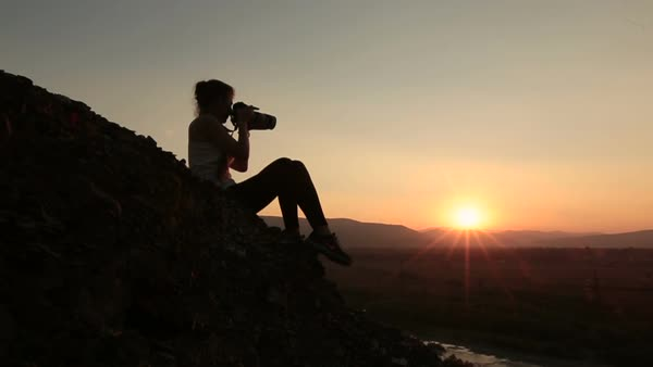 Silhouette of woman photographer taking photos of sunset in the Alpine mountains. Royalty-free stock video