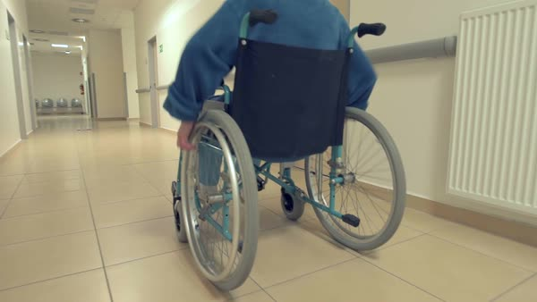 Alone senior in wheelchair in hospital hallway stabilized tracking gimbal shot Royalty-free stock video