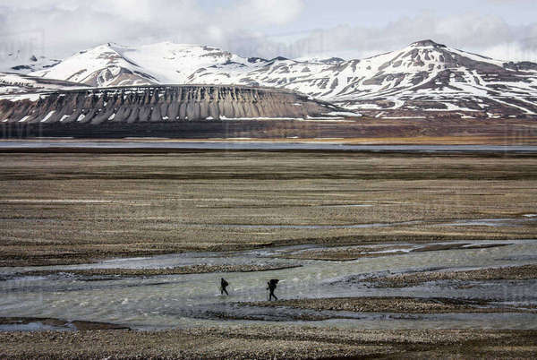 Men crossing river in front of mountains, Svalbard, Norway, July. Rights-managed stock photo