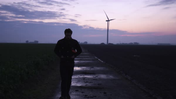 Hand-held shot of a man walking in a field at dawn Royalty-free stock video