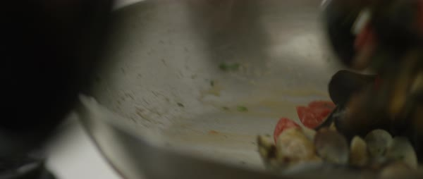 Panning shot of a chef tossing tomatoes and mussels in a frying pan Royalty-free stock video